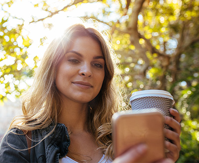 Lady using cell phone while holding coffee